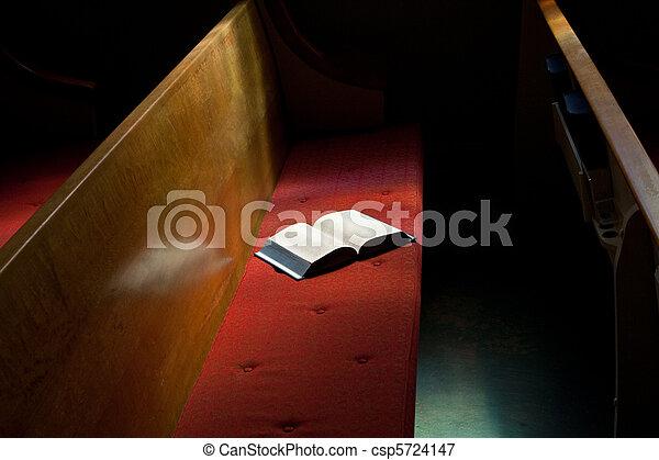 Open Bible Lying on Church Pew in Narrow Sunlight Band - csp5724147