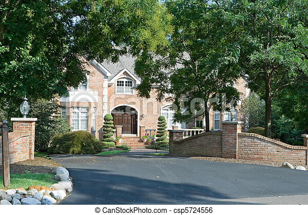 Upscale single family house with extensive landscaping and gate in suburban Philadelphia, PA.  House framed by trees. - csp5724556