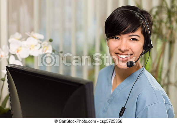 Attractive Multi-ethnic Young Woman Wearing Headset and Scrubs - csp5725356