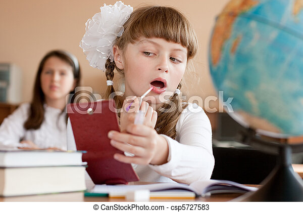 Cute preteen schoolgirl is making make-up during lesson at school - csp5727583