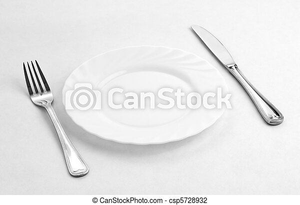 Place setting for one person. Knife, white plate and fork. - csp5728932