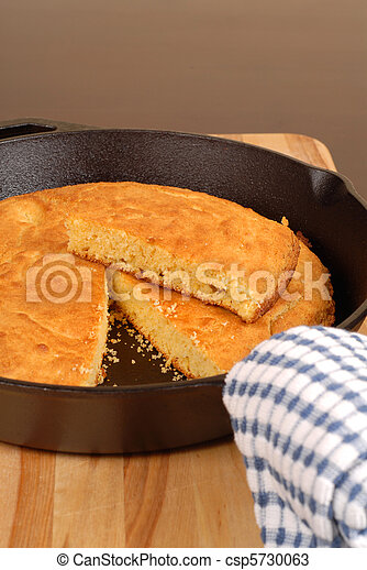 Cornbread in a cast iron skillet with piece cut out - csp5730063