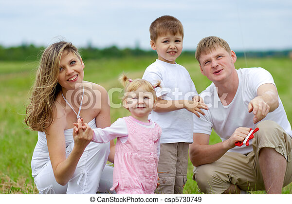 Happy family fly a kite together in summer field - csp5730749