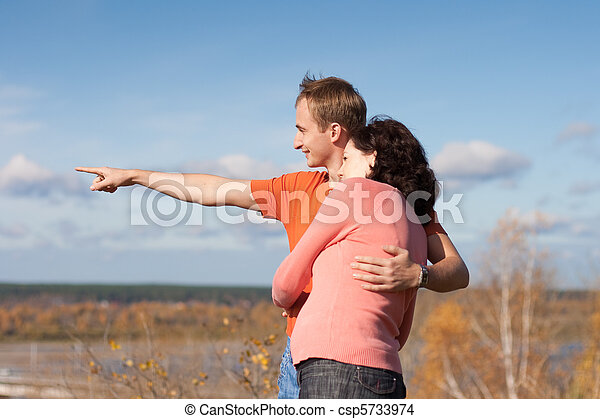 Young man shows to his pregnant wife their future home location - csp5733974