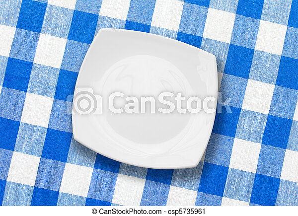 white plate on blue checked fabric tablecloth - csp5735961