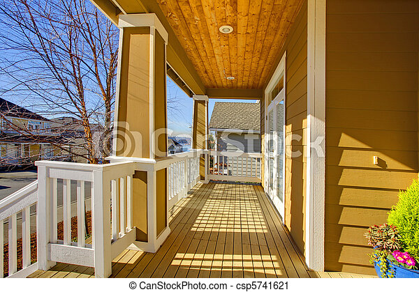 Front sunny happy yellow porch with white trim. - csp5741621