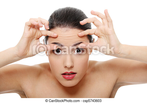 Woman checking her wrinkles on her forehead - csp5743603