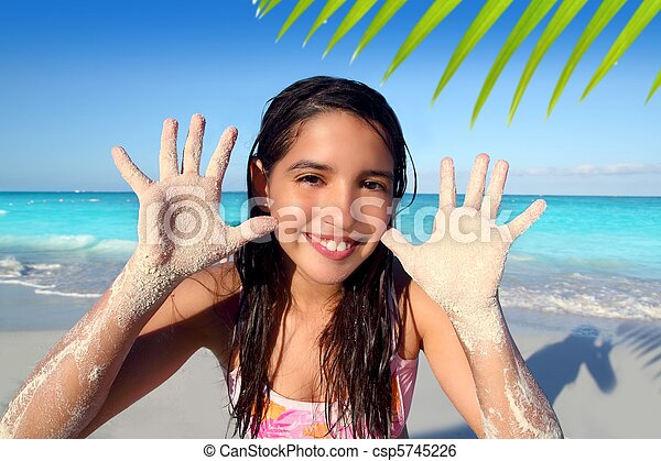 latin indian teen girl playing beach showing sandy hands in Caribbean