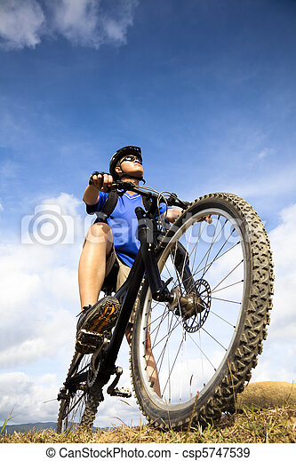 Mountain Biker and blue sky background - csp5747539