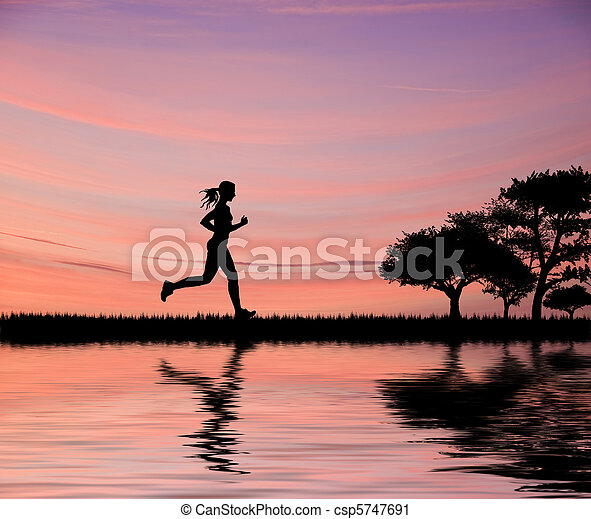 Woman jogger silhouette against beautiful sunset sky running through fields - csp5747691
