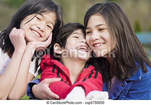 Two sisters and their disabled little brother sitting together at the park, biracial part Thai- Scandinavian descent. - csp5750630