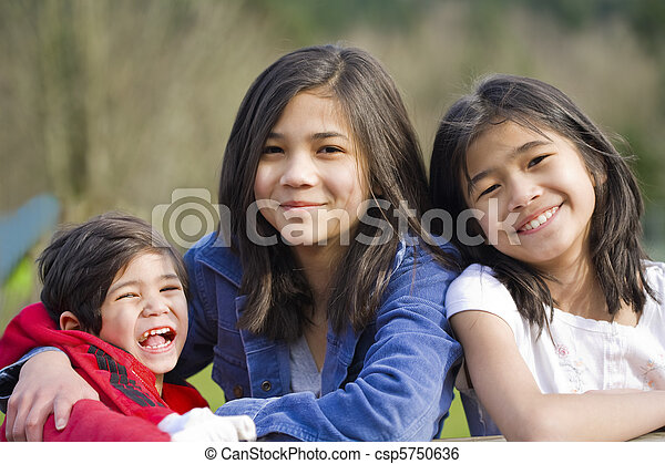Two sisters and their disabled little brother sitting together at the park, biracial part Thai- Scandinavian descent. - csp5750636
