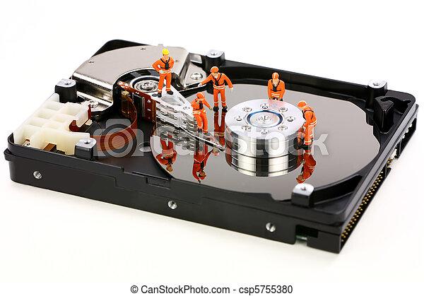 Miniature technicians work on hard drive - csp5755380