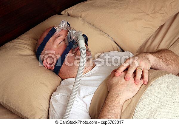 Man with sleep apnea using a CPAP machine - csp5763017