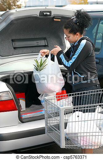 woman putting groceries in trunk - csp5763371