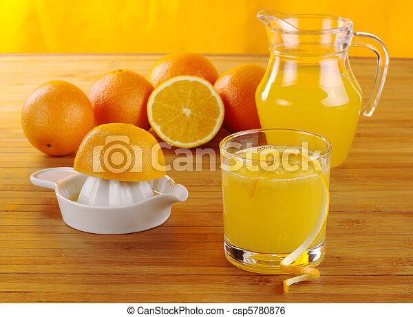 Fresh orange juice with orange juice squeezer, oranges and a jar of orange juice on wooden mat with orange background (Selective Focus) - csp5780876