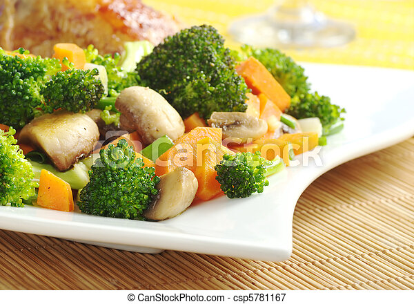 Fried vegetables (broccoli, mushroom, carrot, shallot) on white plate with chicken meat and wine glass in the background (Selective Focus, Focus on the vegetables in the front) - csp5781167