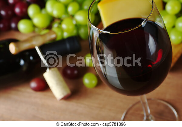 Red wine in wine glass with grapes, cheese a wine bottle and a corkscrew with cork in the background (Selective Focus, Focus on the front of the rim of the wine glass) - csp5781396