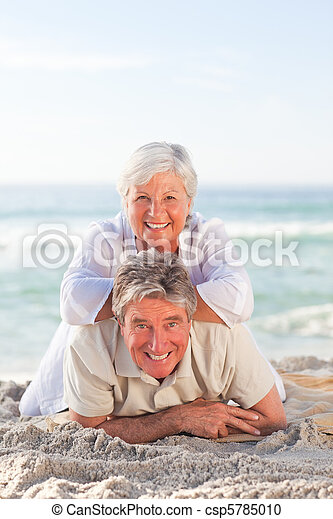 Elderly couple lying down on the beach - csp5785010