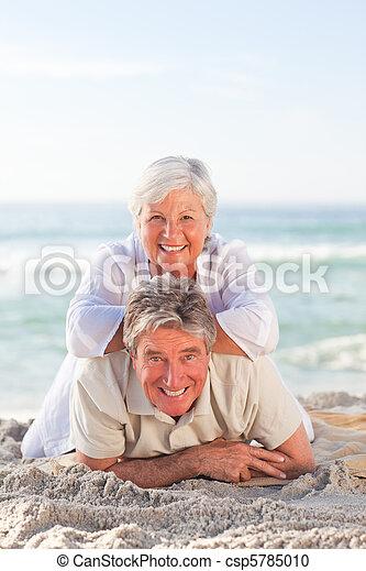 Elderly couple lying down on the beach - csp5785010