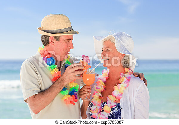 Elderly couple drinking a cocktail on the beach - csp5785087