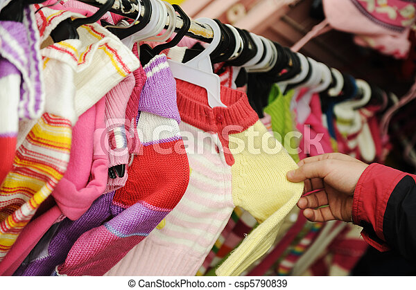Close-up of a female  customer looking for children clothes in a fashion store - csp5790839