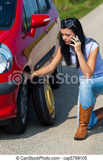 Woman with a flat tire in car - csp5799105