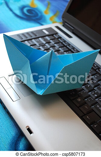 Paper boat sailing on laptop - csp5807173