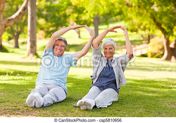 Elderly couple doing their stretches in the park - csp5810656