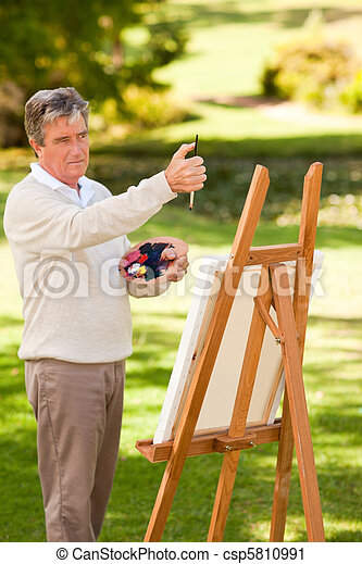 Elderly man painting in the park - csp5810991