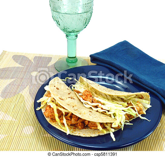 Two fish tacos made with corn tortillas, fish, and cabbage on a blue plate with a blue napkin and aqua beverage glass on a flowered bamboo placemat on a white background - csp5811391