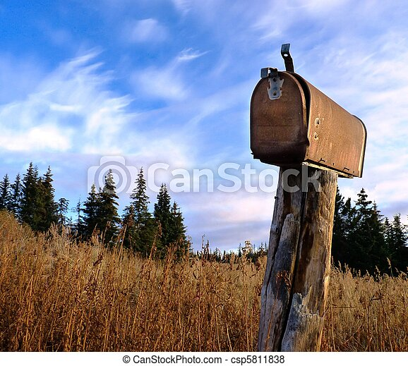 A rusty old rural mailbox on a wooden post in dry grass with spruce in the background and a bright blue sky with clouds - csp5811838