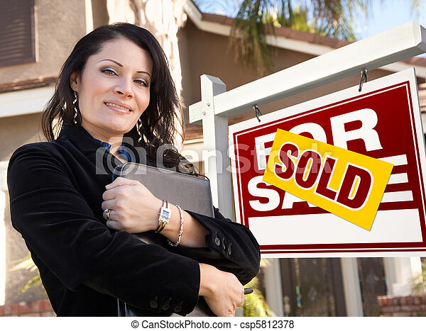 Proud, Attractive Hispanic Female Agent In Front of Sold For Sale Real Estate Sign and House. - csp5812378