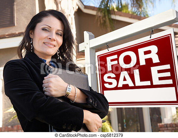 Proud, Attractive Hispanic Female Agent In Front of For Sale Real Estate Sign and House. - csp5812379
