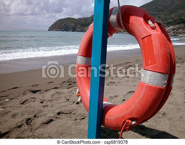 Red lifebelt on the beach - csp5819378