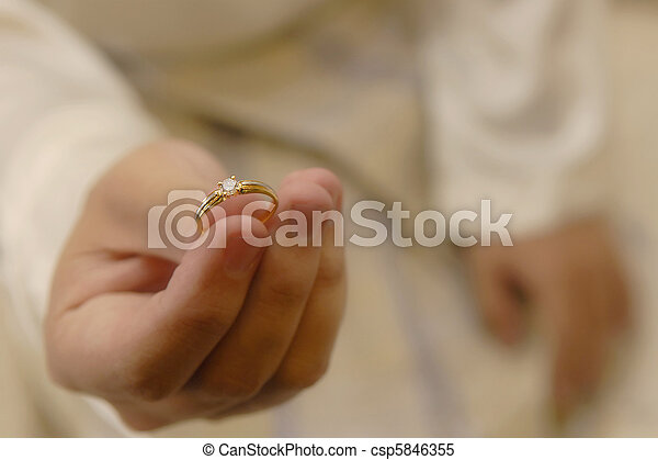 Mans Hand Holding a Wedding Ring - csp5846355