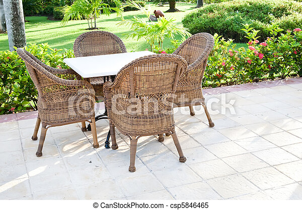 Brown wooden chairs an tables on patio - csp5846465