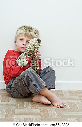 Lonely child sits on the floor holding his soft toy - csp5849322