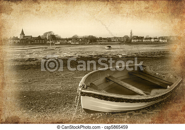 Rowing boat in foreground on low tide harbour at sunset with grunge retro 35mm effect treatment applied - csp5865459