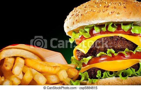 Tasty hamburger and french fries on a dark - csp5884815