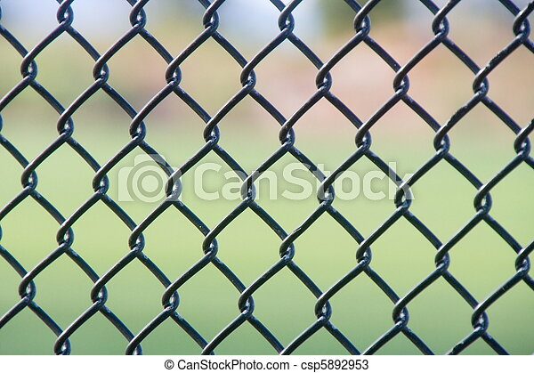 A black chain link fence with an out of focus green background