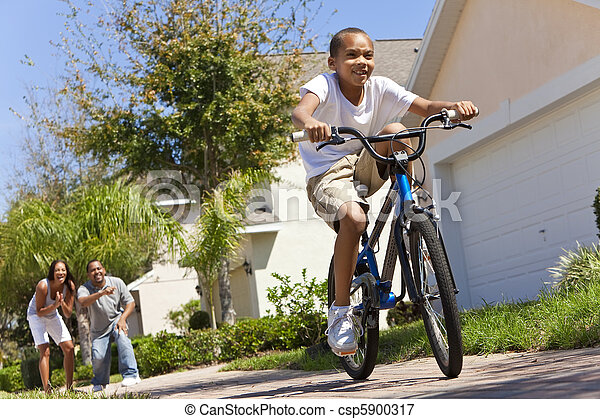 African American Family WIth Boy Riding Bike & Happy Parents  - csp5900317