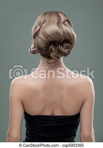 a head and shoulders image of a young woman, from the back. her hair is long and blonde and she is showing an interesting, wavy hairstyle. - csp5903365