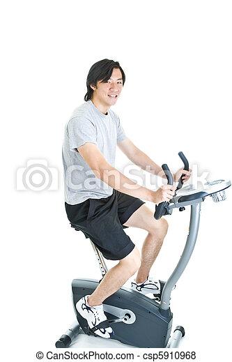 Asian Man Riding Stationary Exercise Bike Isolated - csp5910968