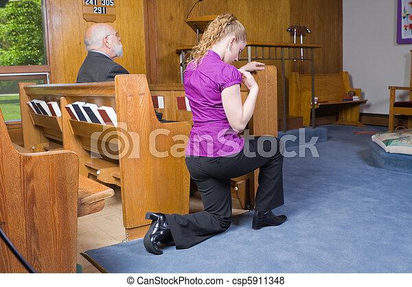Caucasian Woman Kneeling Crossing Herself Church - csp5911348