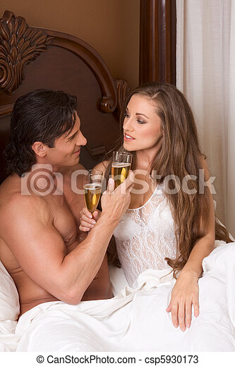 Loving young sensual couple with Champagne in bed - csp5930173