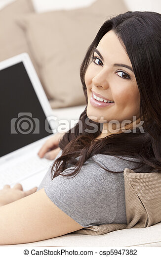 Happy Hispanic Woman Using Laptop Computer - csp5947382
