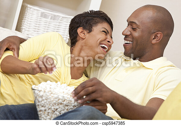 A happy African American man and woman couple in their thirties sitting at home laughing, eating popcorn and watching a movie together - csp5947385