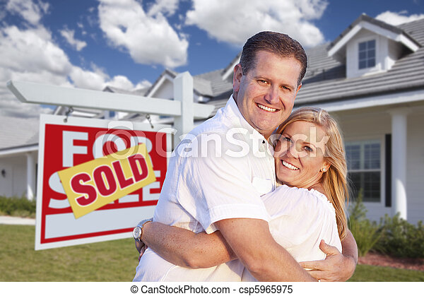 Couple Hugging in Front of Sold Sign and House - csp5965975