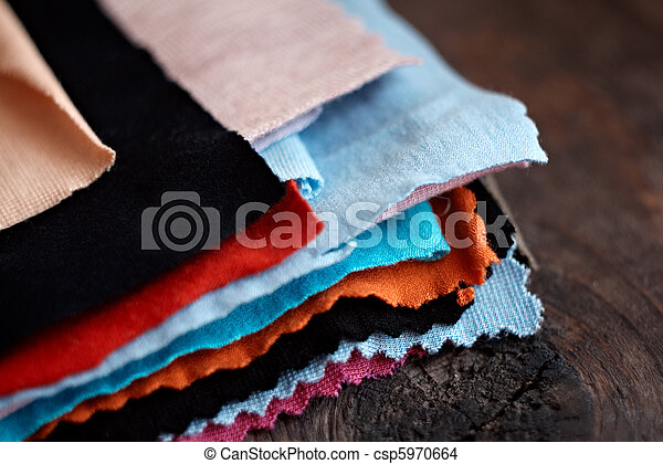 Tissue colored materials, on wood background. Closeup shot. - csp5970664
